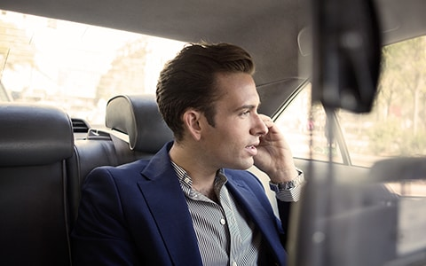 Male professional on the phone in the back of a car