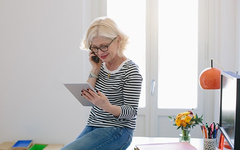lady sitting on desk on phone whilst holding tablet